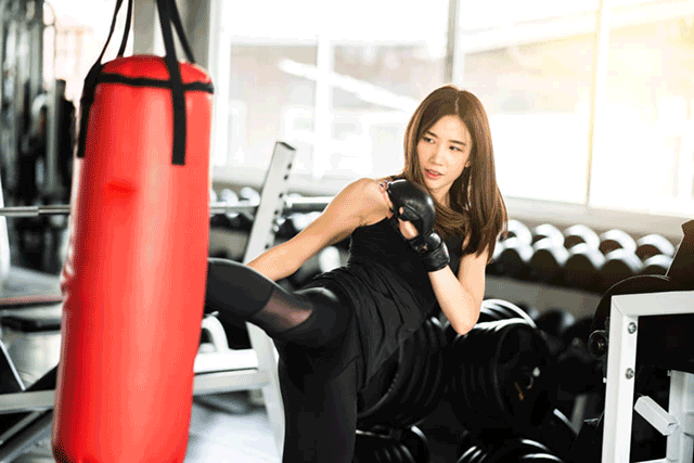 サンドバッグを蹴っている女性キックボクサー