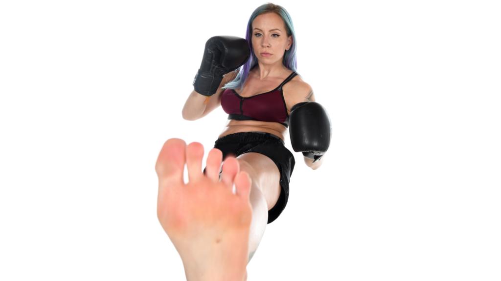 前蹴りを打つ女性格闘家