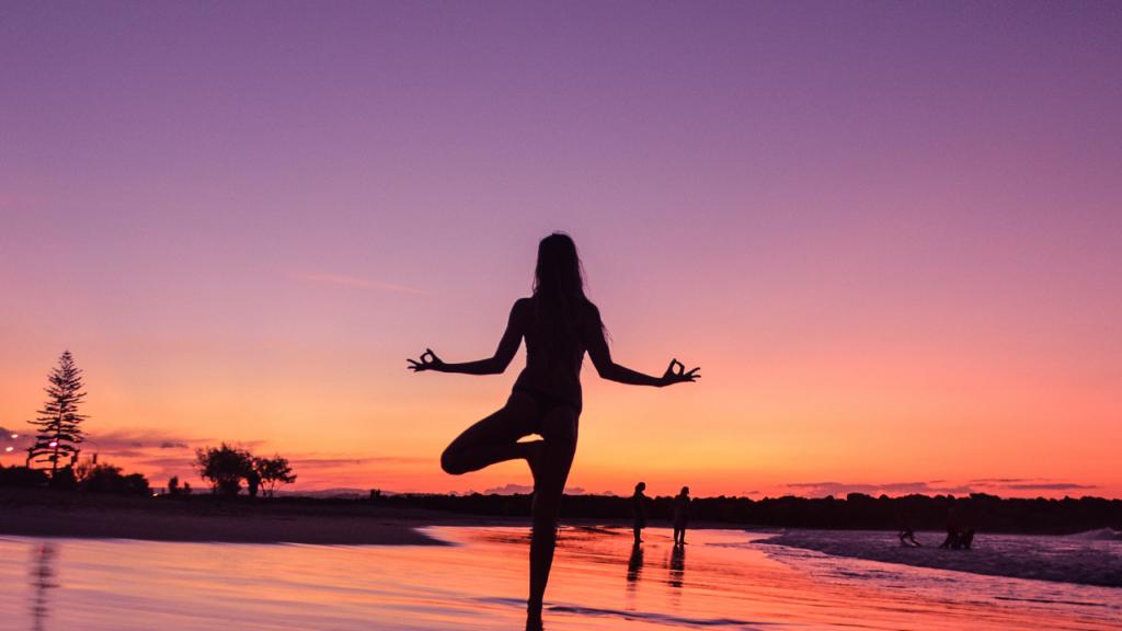夕焼けの海でヨガをする女性