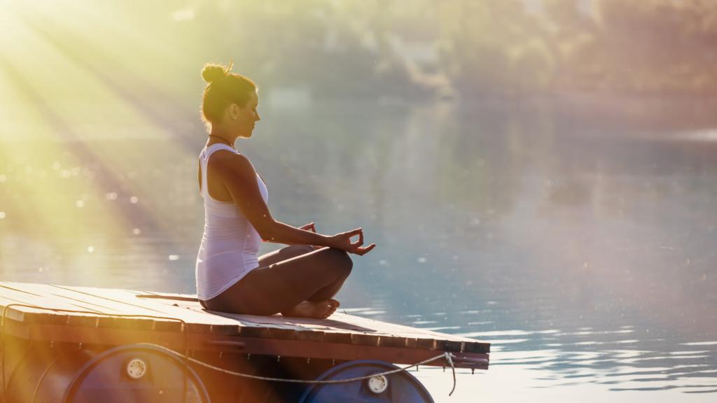 川に向かってヨガをする女性