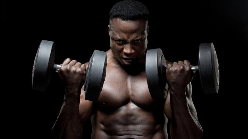 筋肥大を目指してアームカールをするトレーニング中の男性